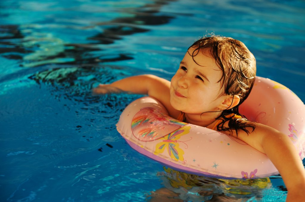 Little cute baby girl in blue water of the swimming pool, summer time for fun