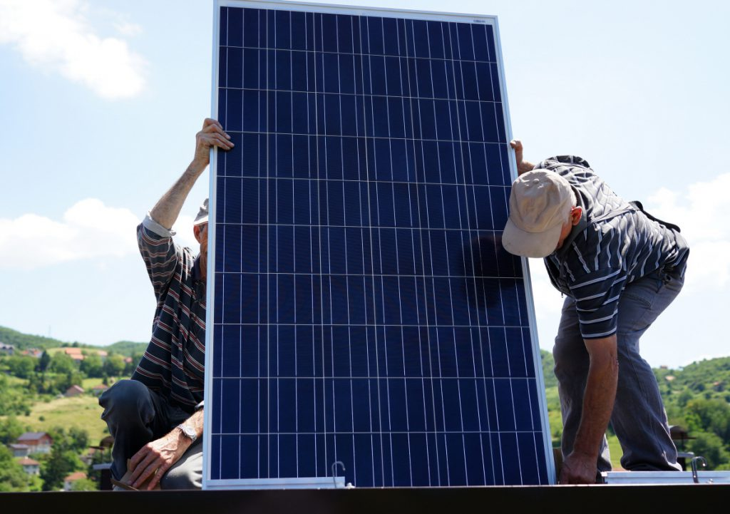 Man installing alternative energy photovoltaic solar panels on r