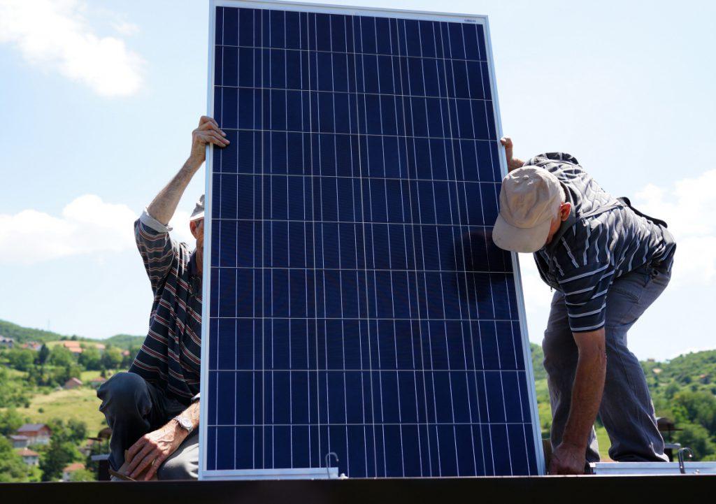Man installing alternative energy photovoltaic solar panels on r
